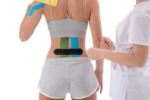 vendaje funcional dinámico con cinta kinesio en la espalda femenina foto