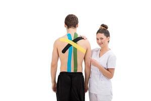 Mujer joven fisioterapeuta aplicando cinta de fisioterapia especial en la espalda del hombre foto