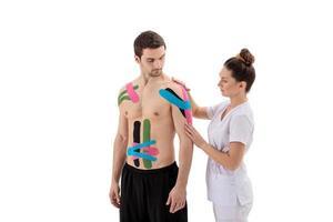 Fisioterapeuta femenina colocando kinesio tape en el hombro del paciente foto