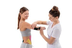 Physiotherapist applying kinesio tape on female patient's arm. Kinesiology, physical therapy, rehabilitation concept. Tennis or golfers elbow treatment. photo