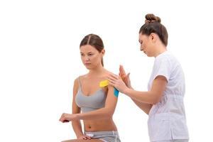 Fisioterapeuta poniendo cinta de kinesio en el hombro de las pacientes aisladas sobre fondo blanco. foto