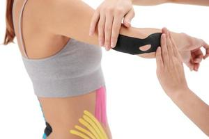 Physiotherapist applying kinesio tape on female patient's arm. Kinesiology, physical therapy, rehabilitation concept. Tennis or golfers elbow treatment. Close up photo