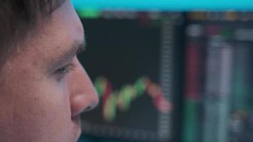 Cara de primer plano de un joven empresario mirando el horario comercial en los monitores. foto