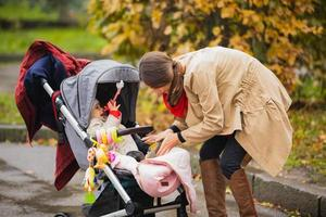 mother is putting small shoes to her Baby in the autumn park photo