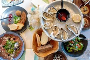 Seafood. Shellfish mussels. mussels with lemon in shells on plate. Restaurant serving fresh oysters on ice. Top view photo