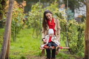 madre sacude a su bebé en un columpio en el parque de otoño. familia feliz pasar tiempo juntos. foto