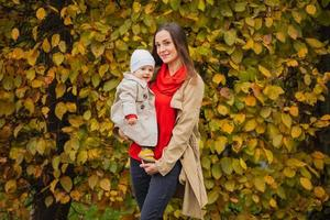 Bay with mom in autumn park. Mom and daughter in the fall. Mom holds the baby in her arms. Mother with her little daughter in the autumn park on a walk. photo