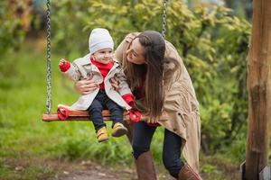 mother shakes her baby on swing at the autumn park. Happy family spend time together. photo