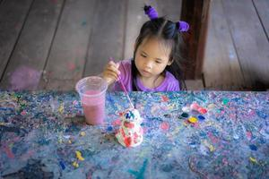 Asian cute little girl having fun to paint on stucco doll photo