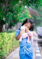 linda niña asiática con una muñeca en el parque foto