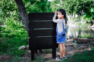 Little Asian girl put mobile phone in pocket with wooden label photo