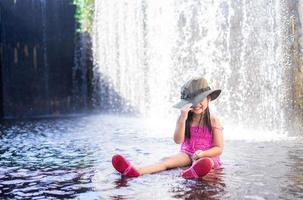 niña asiática usa sombrero jugando cascada en vacaciones foto