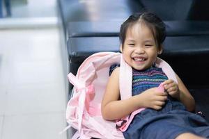 Niña asiática con mochila acostado en el sofá listo para volver a la escuela foto