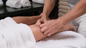 cierre extremo del osteópata aplicando presión con el pulgar sobre el músculo de la pantorrilla femenina. foto