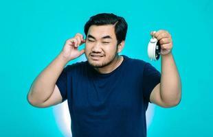 Retrato de un hombre asiático reteniendo el sonido de una alarma con las manos sobre los oídos foto