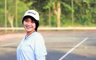 Hermosa mujer asiática con pelo corto, con sombrero y una amplia sonrisa en la cancha de tenis foto