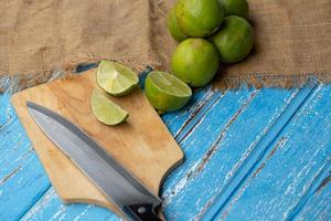Lime juice and lemon on a blue wooden table photo