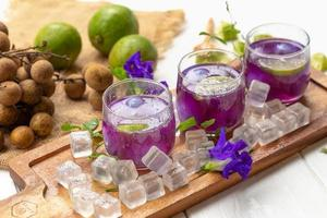 Glass of lemon juice, Pea flowers and Longan on white wooden table photo