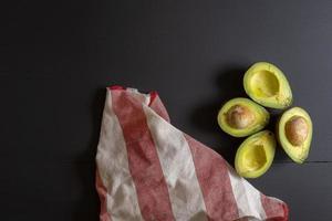 Fresh organic avocado sliced in half on black wooden table photo