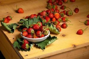 Fresas frescas en un recipiente de cerámica blanca sobre una mesa de madera sobre un fondo negro foto