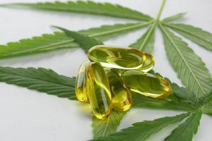 Cápsulas de aceite esencial de cannabis sobre fondo blanco. foto