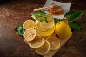 Lemon juice with honey on wooden table,  lemons and sage leaves photo
