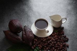 Hot chocolate and Cocoa pod cut exposing cocoa seeds on dark table, top view with copy space photo