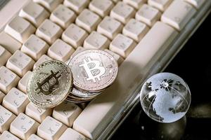Glass globe and Bitcoin Cryptocurrency on keyboard. Business concept photo