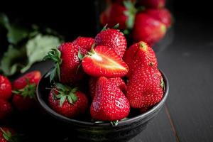Ripe red strawberries on black wooden table photo