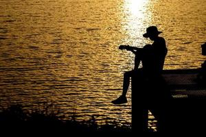 Silhouette of guitarist playing a guitar on the river under the sunset photo