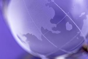 Globe is made of glass on a purple background. Glass globe. Globalization concept photo