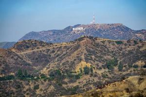 famous hollywood sign on a hill in a distance photo