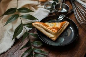 Tuna pie with ceramic plate on a wooden table photo