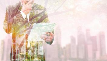 Double exposure of success businessman using tablet with city landscape background. Nature and Building construction. Mixed media photo
