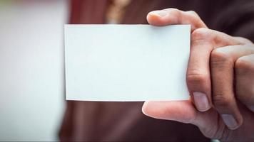 Businessman holding white business card. Mockup bank paper for ads and text. photo