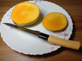 mango en rodajas con cuchillo en un plato foto