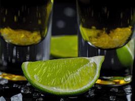 dos tragos de tequila dorado con jugosa lima y sal marina foto
