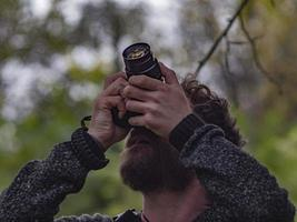bearded hipster man makes photo on camera