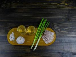 two glasses of cold vodka on a wooden board photo