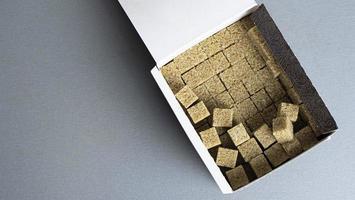 Azúcar de caña refinado en una caja sobre un fondo gris foto