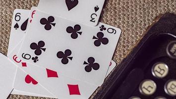 jugando a las cartas sobre fondo de arpillera cerca de una máquina de escribir. fondo de pantalla foto