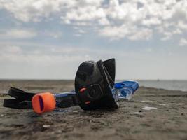 Máscara de buceo negra y snorkel en un muelle de hormigón con el telón de fondo del cielo azul y las nubes foto