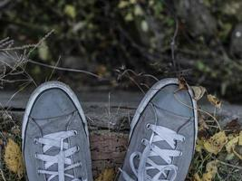 gray sneakers on the legs of a man against a background of fall foliage photo