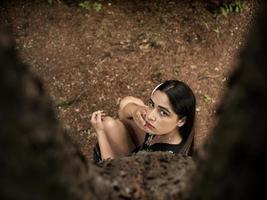 Attractive girl of Caucasian appearance sitting near a tree, holding a hand near the face. view from above photo