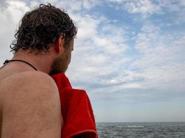 a man with a beard wipes off a towel after swimming in the sea.back view photo