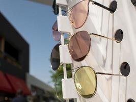 sun glasses on the counter. three pairs of sunglasses in different colors photo