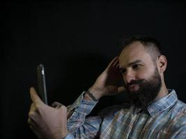 Hombre elegante con barba y bigote posando y tomando un selfie en el teléfono sobre un fondo negro foto