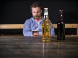 Two bottles of beer are standing on the table against the background of a sitting man who looks into the phone photo