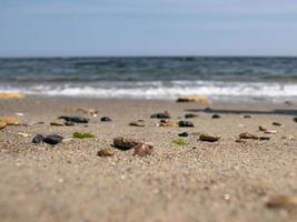 Guijarros de mar y conchas en la orilla del mar contra el cielo azul foto