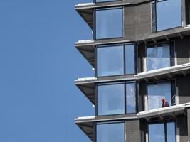 builder in helmet on the floor of a high-rise building under construction against the blue sky photo